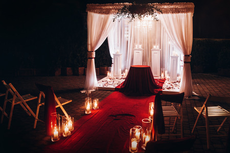 wedding evening ceremony, venue aisle with candles in glass lanterns and arch, stylish wedding decoration for night ceremony in garden, lights. beautiful romantic place for love celebration Stock Photo