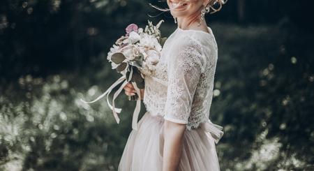 stijlvolle bruid met boeket en geweldige moderne jurk. bruid poseren en glimlachend in zonnige tuin, lippen en oorbellen close-up. fijne kunsthuwelijksfoto, romantisch ogenblik, lange rand Stockfoto