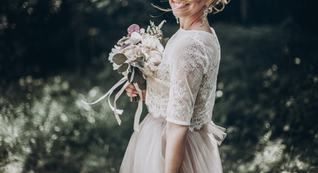 stylish wedding bride with bouquet and amazing modern dress. bride posing and smiling in sunny garden, lips and earrings close up. fine art wedding photo, romantic moment, long edge