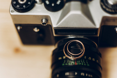 wedding rings on old photocamera. wedding photographer concept, space for text Stock Photo
