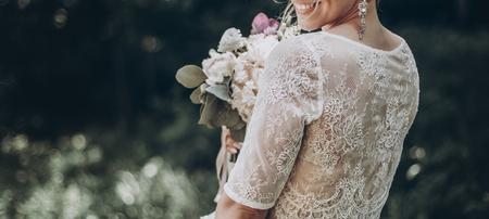 elegante sposa da sposa con bouquet e sorprendente abito moderno. sposa in posa e sorridente in giardino soleggiato, labbra e orecchini da vicino. foto di matrimonio d'arte, momento romantico, bordo lungo