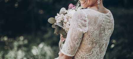 stylish wedding bride with bouquet and amazing modern dress. bride posing and smiling in sunny garden, lips and earrings close up. fine art wedding photo, romantic moment, long edge Reklamní fotografie - 80870040