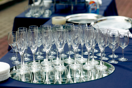 champagne glasses on table at wedding reception outdoors. empty glasses for champagne drinks on tray at celebration in park