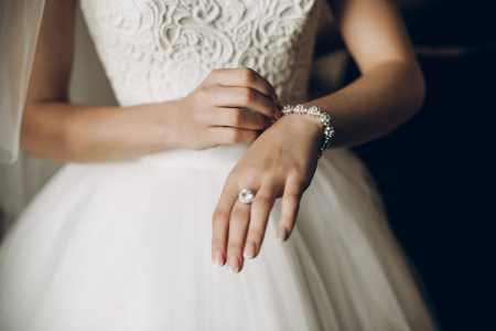 bride putting on luxury bracelet on hand in the morning, getting ready Stok Fotoğraf