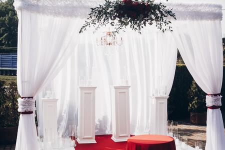 白と赤のアーチと公園での結婚披露宴で通路 写真素材