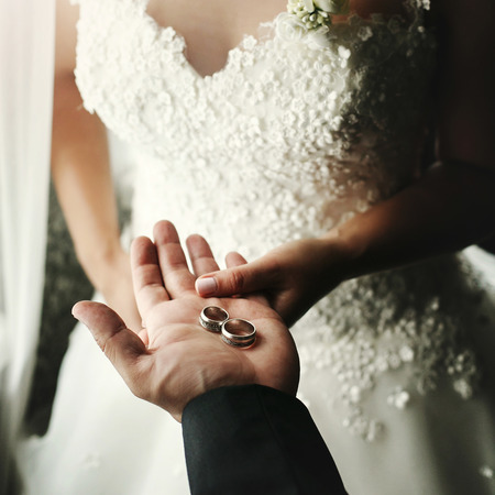 wedding couple holding luxury wedding rings, groom showing bride wedding rings on hand in morning hotel room