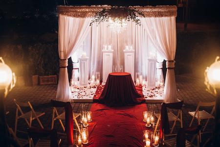 Decoración de noche de bodas para ceremonia, pasillo de lugar con velas en linternas de vidrio y arco, decoración de boda con estilo para la ceremonia de la noche en el jardín, luces. hermoso lugar romantico Foto de archivo - 80897582
