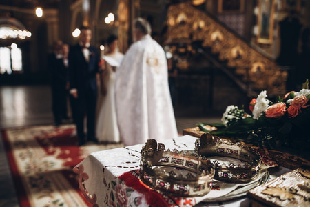 祭壇、司祭は、教会結婚式、宗教伝統のカップルの手で黄金の結婚指輪を入れて黄金の冠