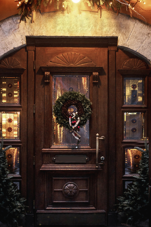christmas wreath on wooden door. luxury decorated store front with garland lights in european city street at winter seasonal holidays