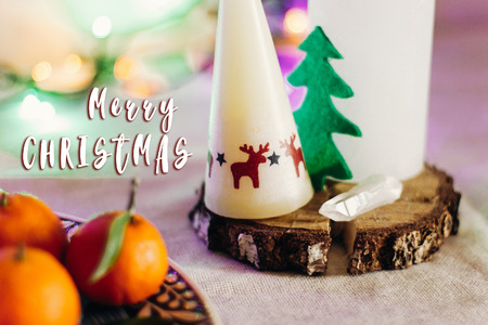 merry christmas text sign on candle with reindeers and tree on rustic christmas table with colorful lights on background. space for text. seasonal holidays greetings