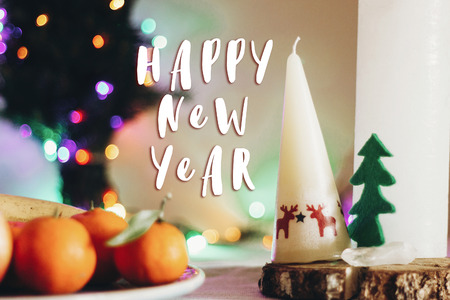 happy new year text sign on christmas rustic table with candle with reindeers and felt tree and fruits on colorful lights background. space for text. seasonal greetings holidays card concept