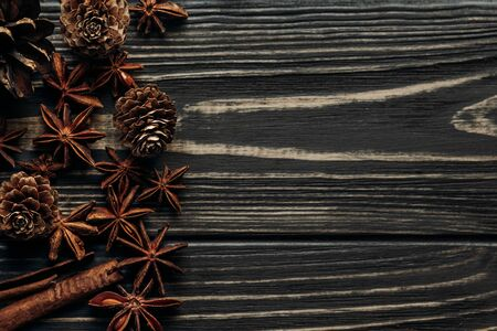 anise and pine cones on wooden background, stylish rustic winter flat lay. space for text. cozy mood autumn. seasonal holidays concept. greeting card