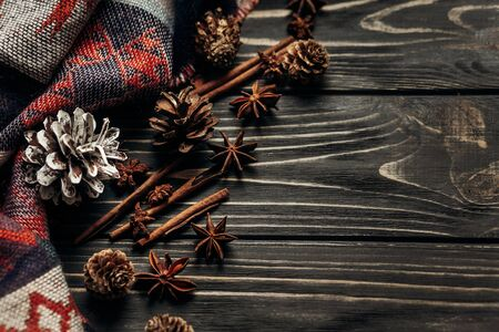 stylish rustic winter or autumn wallpaper with anise cinnamon and pine cones on wooden background. space for text. cozy mood. seasonal holidays concept Banco de Imagens