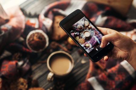hand met telefoon nemen foto van stijlvolle winter plat lag koffie koekjes en specerijen op houten rustieke achtergrond. gezellige gemoed herfst