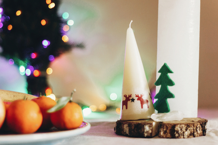 christmas rustic table with candle with reindeers and felt tree and fruits on colorful lights background. space for text. seasonal greetings holidays card concept Stock Photo