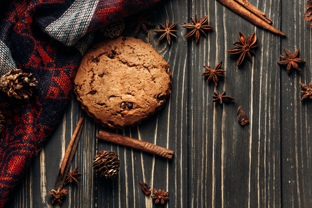 cookie anise cinnamon and pine cones on wooden background, stylish rustic winter flat lay. space for text. cozy mood autumn. seasonal holidays concept