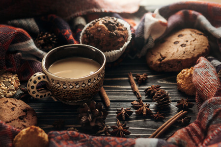 stylish rustic winter coffee cookies and spices on wooden background in morning. space for text. cozy mood autumn. seasonal holidays concept