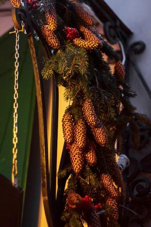 pine cones wreath and garland lights on front door in city street. seasonal decorations
