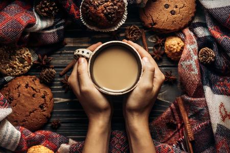 handen met koffie koekjes en specerijen op houten rustieke achtergrond. stijlvolle wintervlakte leggen. ruimte voor tekst. gezellige gemoed herfst. seizoensgebonden vakantie concept.