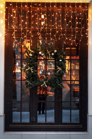 ウィンドウに珍しいクリスマスの花輪を捧げる。冬季節の休暇でヨーロッパの街のガーランド ライトと豪華な装飾の店の前
