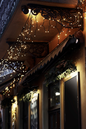luxury decorated store front with garland lights in european city street at winter seasonal holidays Banque d'images