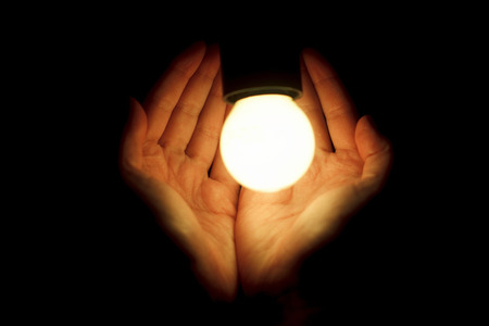hands of human holding illuminated led bulb on black background. eco safe the planet concept. new idea or energy theme. space for text Banco de Imagens