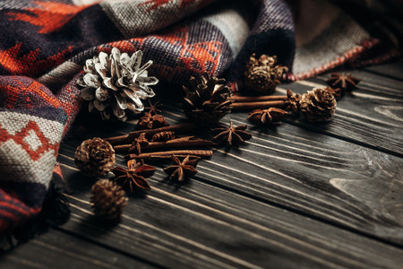 stylish winter or autumn wallpaper. anise cinnamon and pine cones on wooden rustic background. space for text. cozy mood. seasonal holidays concept