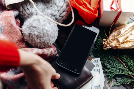 christmas shopping concept. hand holding wallet and phone with empty screen . seasonal sale. rustic background with wallet and bags of presents. advertising app with space for text