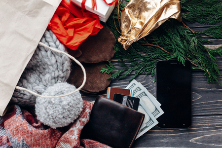christmas shopping concept. big sale. seasonal rustic background with phone with empty screen money wallet and bags of  presents. advertising app with space for text Stock Photo