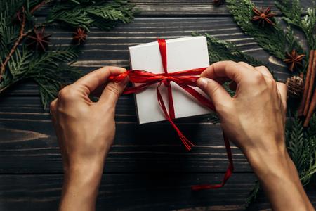 mani che avvolgono il regalo di Natale con il nastro rosso sul piano in legno elegante giaceva con rami verdi. spazio per il testo. concetto di cartolina d'auguri. saluti stagionali per le vacanze invernali Archivio Fotografico