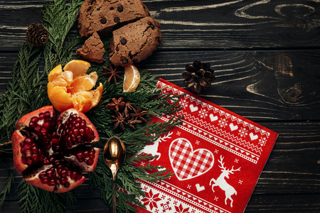 reindeer traditional napkin gingerbread cookies garnet oranges and spices on fir branches on rustic wooden background, stylish winter flat lay.space for text. greeting card. seasonal holidays concept Фото со стока