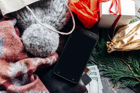 credit cards money wallet and phone with empty screen on wooden rustic background with bags presents. christmas shopping concept. seasonal sale. advertising app with space for text