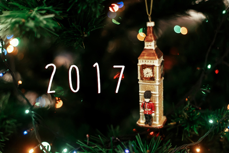 2017 sign text on Queens guard near big ben christmas ornament, cute toy soldier near golden watch clock english christmas decoration close-up, surrounded by colorful lights