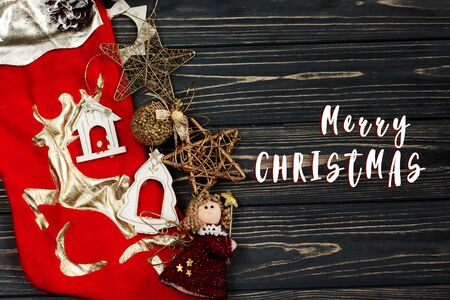merry christmas text sign on christmas golden stylish toys. ornament border on black rustic wooden background. space for text. holiday greeting card concept. unusual creative top view