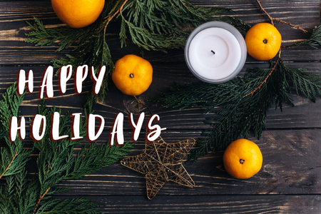 happy holidays text sign on christmas flat lay wallpaper with green branches and oranges and golden star on black rustic wooden background. seasonal greeting card and advertising concept Stock Photo