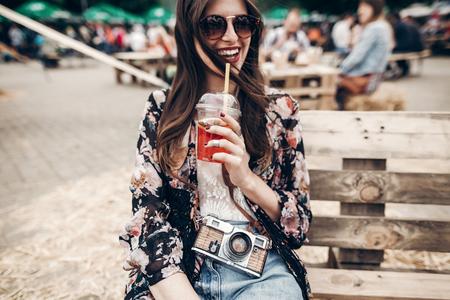 レモネードとサングラスで幸せなスタイリッシュな流行に敏感な女性。祭では屋台の食べ物の木製のベンチに座ってカクテルを保持しているデニム