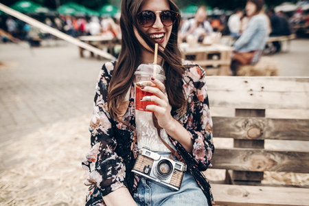 happy stylish hipster woman in sunglasses with lemonade. boho girl in denim and bohemian clothes, holding cocktail sitting on wooden bench at street food festival. summertime. summer vacation