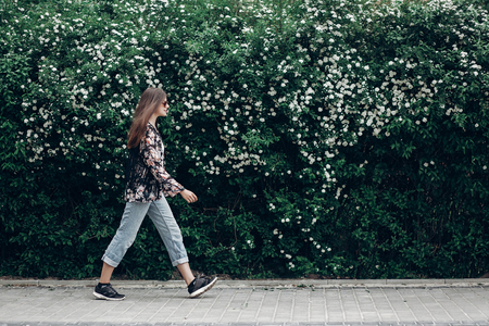hipster woman in sunglasses walking on background of blooming bush with white flowers of spirea. boho girl outing in floral and denim modern clothes in summer city street. space for text