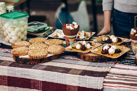 tasty cookies and cakes with creamy cupcakes on table, space for text. street food festival. candy bar at wedding reception, catering outdoors.  summer picnic
