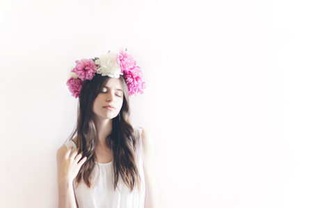 hipster woman with peonies wreath and in white dress posing in white room. sensual boho bride with peony crown, relaxing in morning, space for text. sensual girl portrait