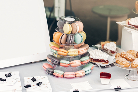 delicious colorful macaroons on pyramid stand and empty board on table at street food festival. candy bar with tasty sweets cakes, catering at wedding reception, celebration, party. summer picnic Stockfoto