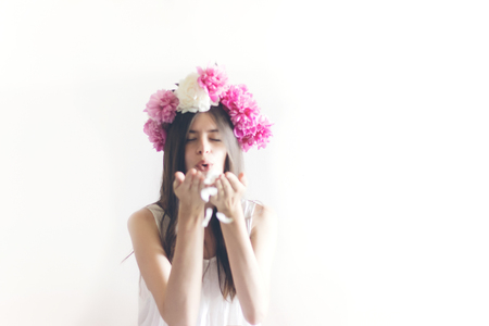 hipster woman with peonies wreath and in white dress posing in white room, holding petals in hands. sensual boho bride with peony crown, relaxing in morning, space for text