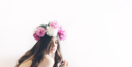 hipster woman with peonies wreath and in white dress posing in morning room. romantic boho bride with peony crown, relaxing moment, space for text. sensual girl portrait