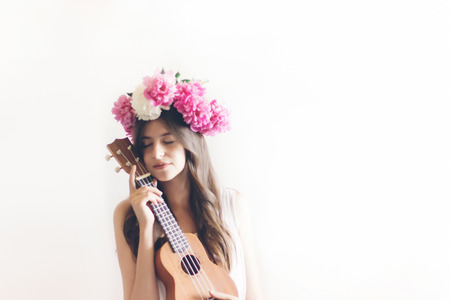 hipster woman playing ukulele, posing in peonies wreath and in white dress. romantic boho bride with peony crown holding guitar, relaxing moment, space for text. sensual girl portrait Archivio Fotografico