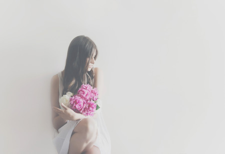 hipster woman in white dress holding pink bouquet of peonies in white room. boho bride with peony bouquet in front, relaxing in morning, space for text. sensual girl portrait