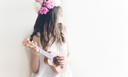 hipster woman playing ukulele, posing in peonies wreath and in white dress. romantic boho bride with peony crown holding guitar, relaxing moment, space for text. sensual girl portrait Stockfoto