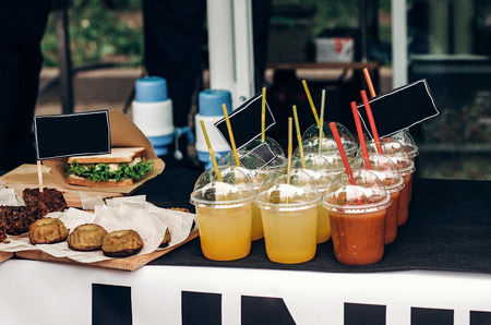 colorful lemonades with empty cards on table, space for text. street food festival. drink bar at reception, catering outdoors. summer picnic. cocktails in plastic cups with straws