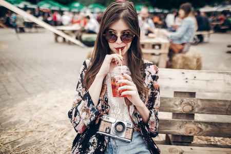 stylish hipster woman drinking lemonade. cool boho girl in denim and bohemian clothes, holding cocktail sitting on wooden bench at street food festival. summertime. summer vacation travel Stockfoto