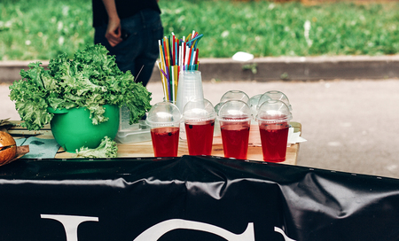 lemonade with strawberry and mint in plastic cups, space for text and green lettuce. street food festival. drink bar at reception, catering outdoors. summer picnic. colorful drinks