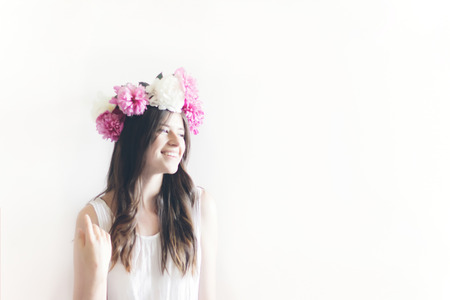 hipster woman with peonies wreath and in white dress smiling in white room. sensual boho bride with peony crown, relaxing in morning, space for text. sensual girl portrait Archivio Fotografico